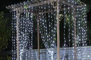 cortina de led iluminando jardin con mesita y cobertizo